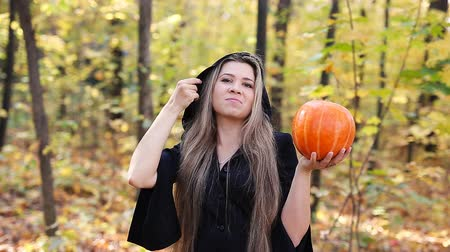 dynia : beautiful witch with a pumpkin in autumn forest Wideo