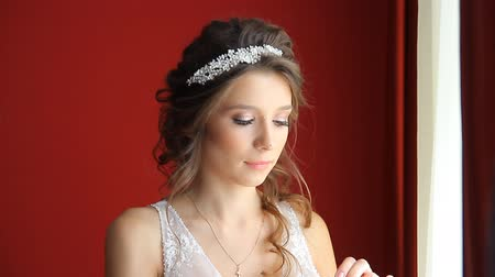 gyöngyszem : beautiful brunette stylish bride getting ready in the morning in the room Stock mozgókép