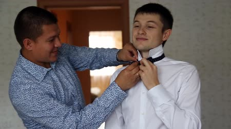tying : Happy groom. Close-up of young man in white shirt adjusting his bow tie and smiling while standing against mirror