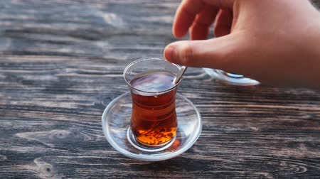 colorful candy : Pouring tea into a cup on a wooden table Stock Footage