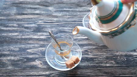 demlik : Pouring tea into a cup on a wooden table Stok Video