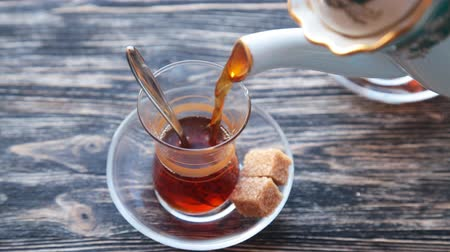 hot beverage : Pouring tea into a cup on a wooden table Stock Footage