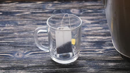 teabag : Glass of tea with teabag and pouring water in slowmotion Stock Footage