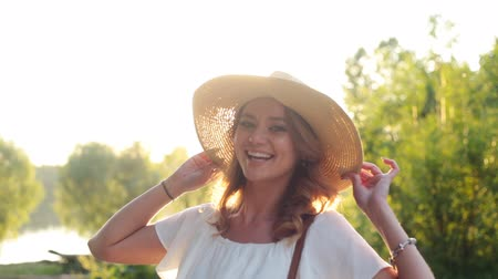 outdoor : Girl in a hat smiling in slow motion