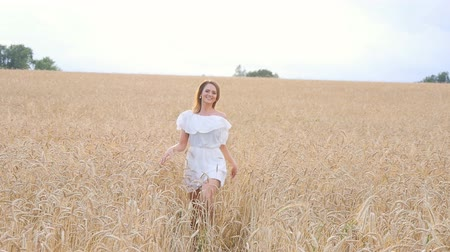 viselet : Young woman girl in white dress running on the Field Stock mozgókép