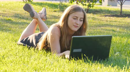 mês : Woman on laptop outside on grass