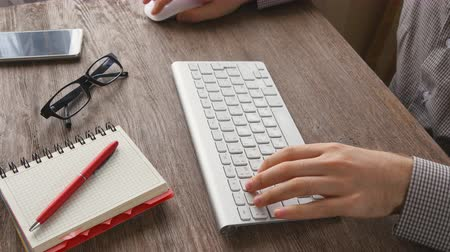 devise : Man arms typing on keyboard at natural hardwood desk Stock Footage