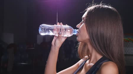 copo : Young fit woman drinking water at gym