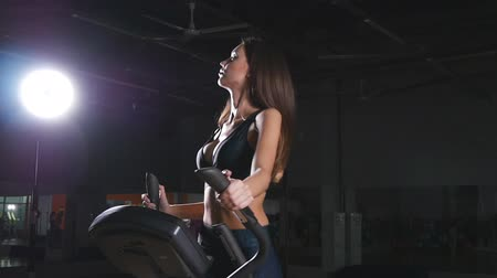 elliptical : Young woman exercising on elliptical machine Stock Footage
