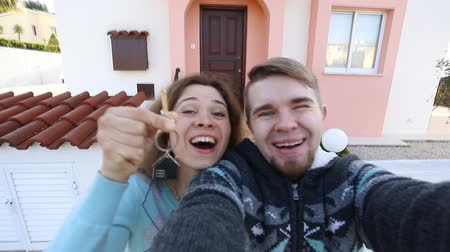 přední : Happy couple showing keys of their new house
