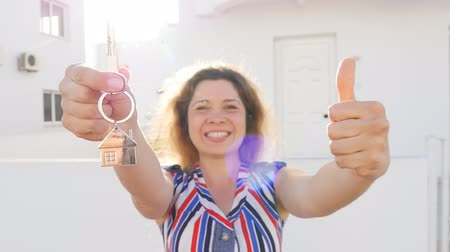 nákupy : Attractive young woman holding keys while standing outdoor against new house.