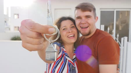 vista frontal : Happy young couple standing outdoors holding key to their new house
