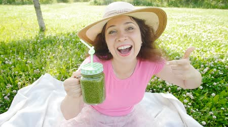 miska : Young woman with green vegetable smoothies in the park