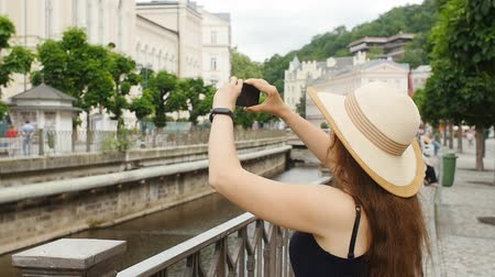 elfog : Traveling girl are using a smart phone to capture the image of the old city