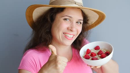 cereal product : Womans hands holding a cup with organic oats and berries