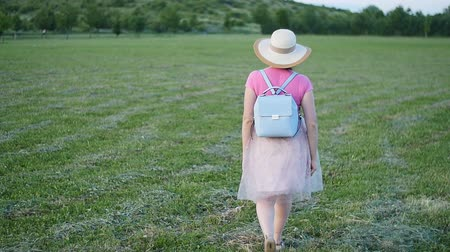 sky only : A young woman in a hat walks the green field