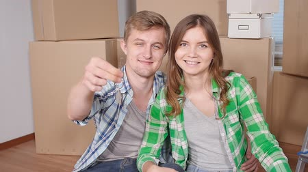 parquete : Young happy couple with boxes and holding flat keys
