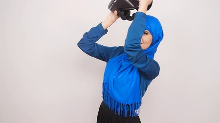 persone : A young Muslim woman with virtual reality glasses