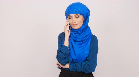 whitebackground : Young Muslim woman talking on cell phone Stock Footage