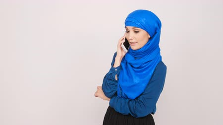 whitebackground : Young muslim woman talking on cell phone