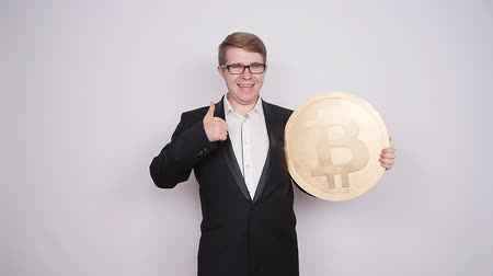 пари : Business man holding big bitcoin in his hands. Cryptocurrency, people, technology, money and future concept Стоковые видеозаписи