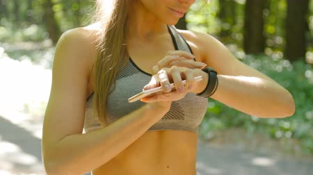 интенсивность : A woman looks at a fitness tracker during a workout Стоковые видеозаписи