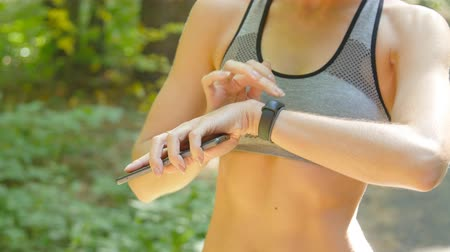 heart rate : A woman looks at a fitness tracker during a workout Stock Footage