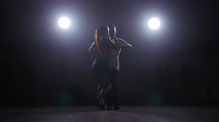 whitebackground : Couple dancing in a dark room in the backlight