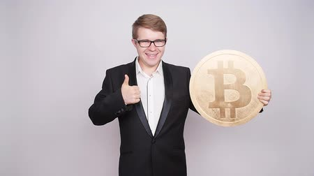 úpadek : A man holds a big coin bitcoin