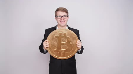снижение : A man holds a big coin bitcoin