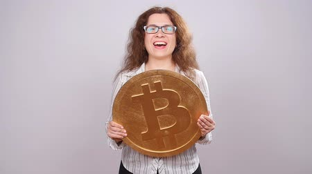 buy gold : Happy woman showing big Bitcoin coin. Virtual money concept. Cryptocurrency Stock Footage