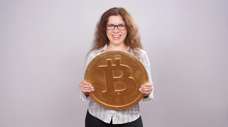 névtelen : Happy woman showing big Bitcoin coin. Virtual money concept. Cryptocurrency Stock mozgókép