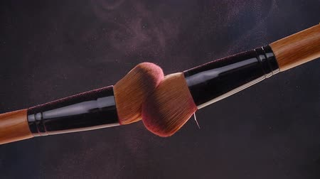 eyeshadow : Two makeup brushes with powder on a dark background
