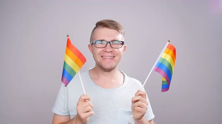 lesbian couple : A man holding a LGBT flag in his hands