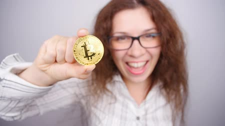 economical : Woman holding a Golden Bitcoin coin