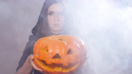 witch hat : Woman witch is standing with the pumpkin in smoke Stock Footage