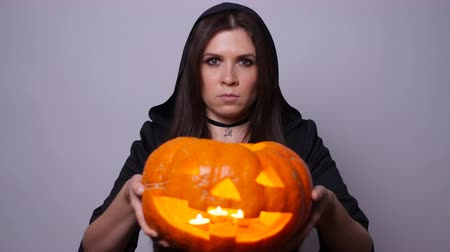 czary : Witch with a carved pumpkin. Halloween concept