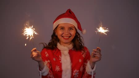desejo : Young santa claus woman in red christmas or new year hat holding sparkler