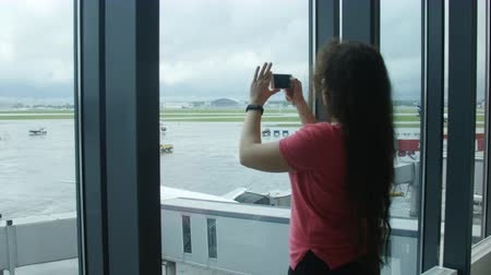gravado : MOSCOW, RUSSIA - MAY 25, 2017. Young Woman taking photo on cellphone in the airport