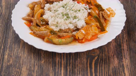 tikka masala : rice with meat and vegetables on wooden table