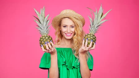 ananas : Happy young blonde woman holding a two pineapple on a pink background