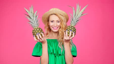 ananás : Happy young blonde woman holding a two pineapple on a pink background