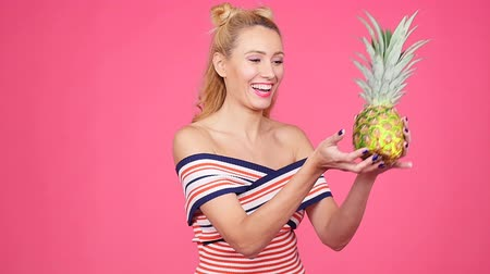 ananás : Young woman holding a pineapple on a pink background
