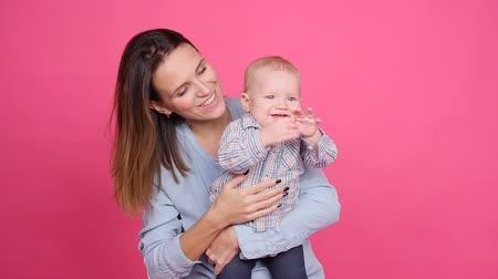 mamãe : Young happy woman hugging her little son on a pink background