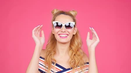 air kiss : Young woman on a pink background with sunglasses