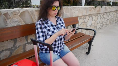bekliyor : Young woman traveler sits and looks at smartphone Stok Video