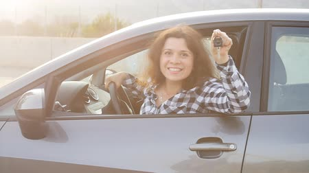 prawo jazdy : Young woman holding the key to a new car