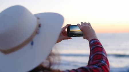 best of : Young woman taking photos on beach during sunset or sunrise