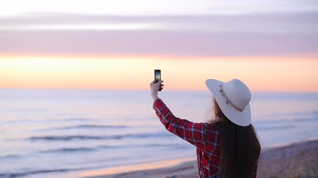 képek : Young woman tourist taking pictures of the sunset or dawn by the sea