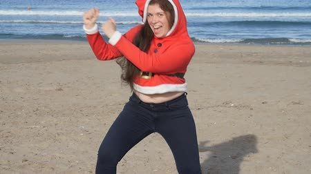 Санта : Cheerful young woman in santa hat dancing outdoors Стоковые видеозаписи